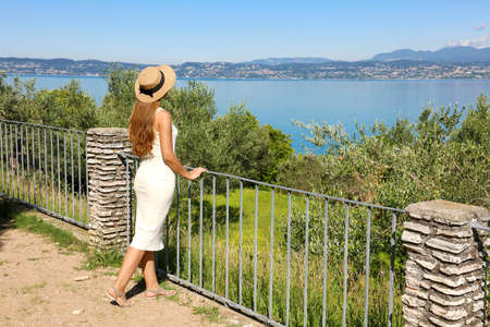 Beautiful tourist woman with hat enjoying view of Lake Garda from Sirmione town, Italy