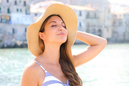 Close up young beautiful woman with hat enjoying sun on the beach. Relaxing sunbathing holidays in Cefalu, Sicily.