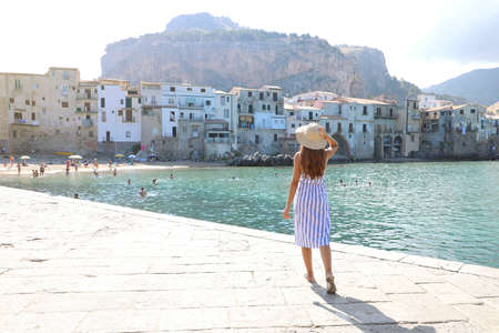 Holidays in Sicily. Back view of woman enjoying view of Cefalu old town on Sicily Island, Italy.