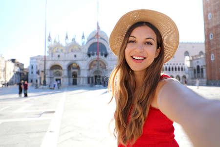 tourist girl on summer vacation taking selfie photo with famous Cathedral in St Mark's Square. European tourism attraction in Italy.