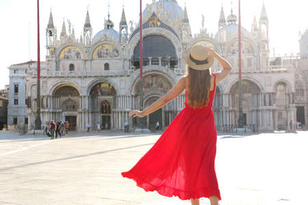 Holidays in Venice. Back view of pretty girl in elegant red dress dancing in St Mark's Square in Venice, Italy. Beautiful young woman visiting Europe.