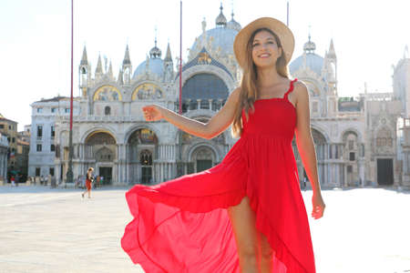 Happy beautiful woman in elegant red dress dancing in St Mark's Square in Venice, Italy. Pretty sexy fashion model girl posing in Venice, Italy. Archivio Fotografico