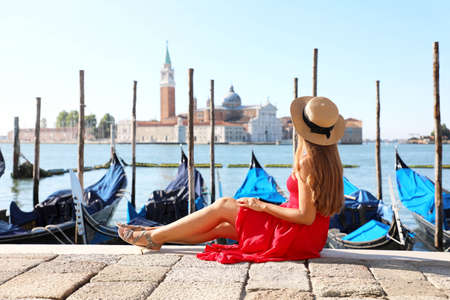 Attractive young woman with hat sitting on the edge of Venetian Lagoon looking at San Giorgio Maggiore church in Venice, Italy