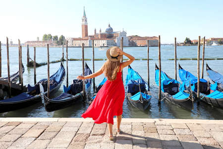 Holidays in Venice. Back view of beautiful girl in red dress enjoying view of Venice Lagoon with the island of San Giorgio Maggiore and gondolas moored. Archivio Fotografico