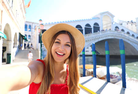 Venice tourist girl on summer holidays taking selfie photo with famous Rialto Bridge. Venice tourist attraction in Italy. Archivio Fotografico