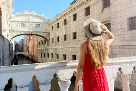 Travel in Venice. Back view of pretty girl in elegant red dress holding hat looking at Bridge of Sighs in Venice, Italy. Beautiful young woman visiting Europe.