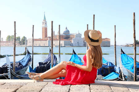 Beautiful young woman with hat sitting on the edge of Venetian Lagoon looking at stunning panoramic view of Venice, Italy Archivio Fotografico