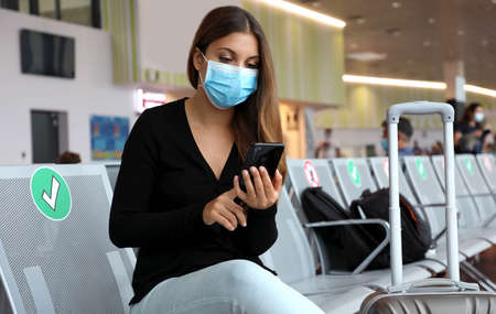 COVID-19 Young tourist woman with surgical mask using phone and sitting respecting social distancing at the airport Archivio Fotografico