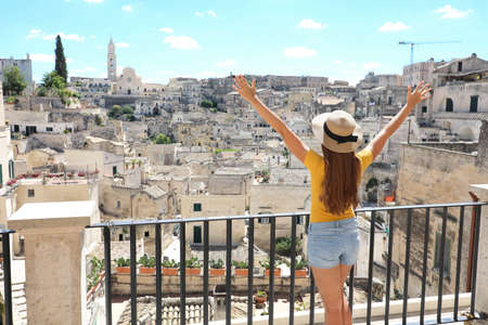 Happy tourist girl with arms raised up enjoys the stunning view of the Sassi di Matera in Italy on a warm summer day. Travel destination, adventure, success and exploration concept.