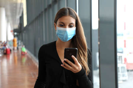 Business woman with surgical mask and mobile phone looks for flight at the airport
