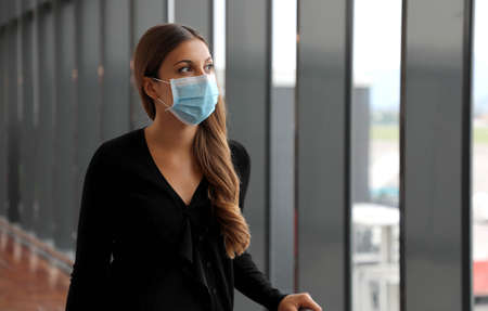 Pensive young business woman wearing face mask while waiting at airport terminal during virus pandemic