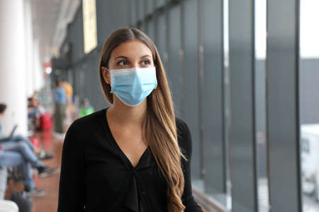 Traveler woman wearing face mask protection walking in public space station or airport