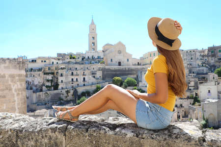 Beautiful young woman with hat sitting on wall looking at stunning panoramic view of Matera, Italy Archivio Fotografico
