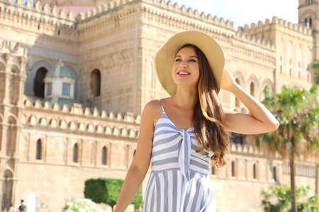 Poatrait of smiling tourist woman in Palermo old town with the Cathedral on the background. Attractive traveler girl visiting Sicily on summer. Vacations in Italy.