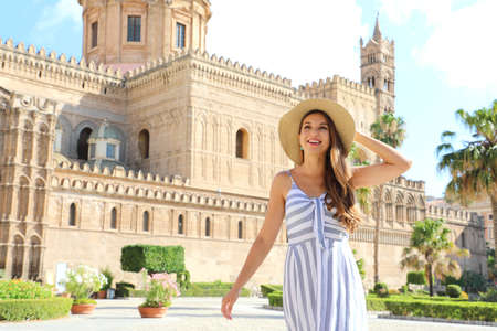 Young smiling tourist woman in Palermo old town with the Cathedral on the background. Attractive traveler girl visiting Sicily on summer. Vacations in Italy. Archivio Fotografico