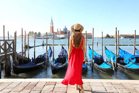Back view of beautiful girl in red dress walking in Venice with gondolas moored