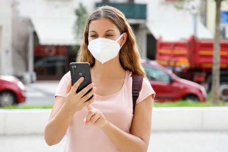 Latin American woman with smart phone wearing face protective mask in the street Archivio Fotografico