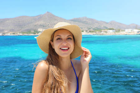 Young cheerful bikini woman with hat looking at camera. Relaxing sunbathing holidays in Favignana Island, Sicily.