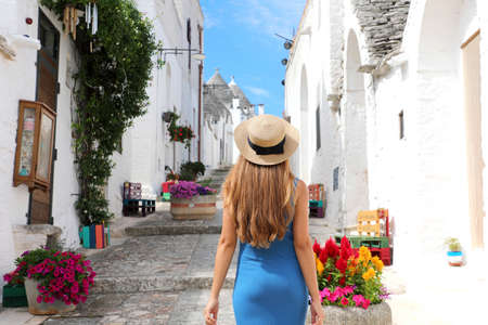 Beautiful tourist girl visiting Alberobello old town with the traditional Trulli houses in southern Italy Archivio Fotografico