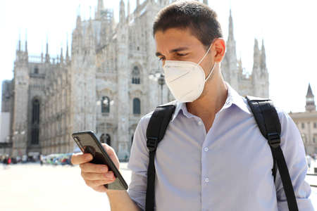 COVID-19 Young man wearing protective mask using smartphone app in Milan, Italy Archivio Fotografico