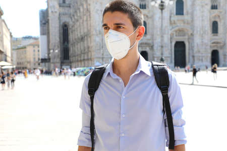 COVID-19 Young business man wearing KN95 FFP2 face mask protective for spreading of Coronavirus in Milan, Italy