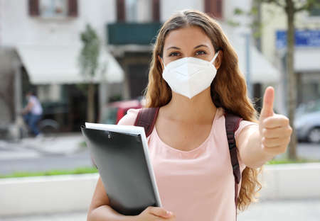 Optimistic student girl back to school with protective mask shows thumb up