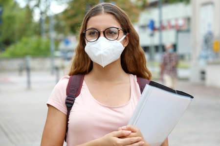 COVID-19 Beautiful student female with protective mask walking in city street. College young woman back to school after pandemic coronavirus.