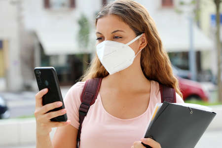 Student female with protective mask reading a message on smart phone in the street