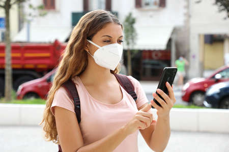 Brazilian woman with smart phone wearing face protective mask in the street