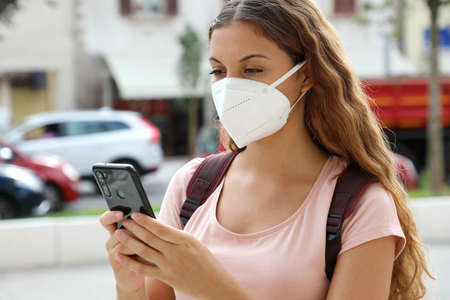 Close up of student female with protective mask messaging with smart phone in city street