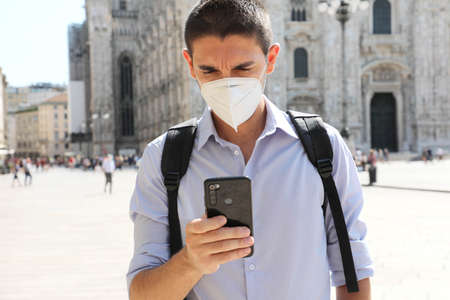 COVID-19 Young man wearing protective mask using smartphone app in Milan, Italy Фото со стока