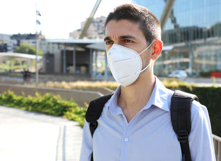COVID-19 Man wearing KN95 FFP2 protective mask in modern city street Archivio Fotografico