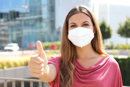 COVID-19 Optimistic business woman wearing protective mask KN95 FFP2 showing thumbs up in modern city street Archivio Fotografico