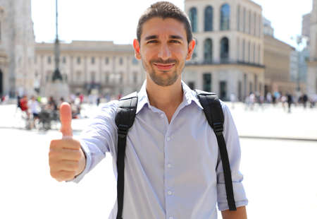Handsome man looking at camera and thumbs up in city street Standard-Bild