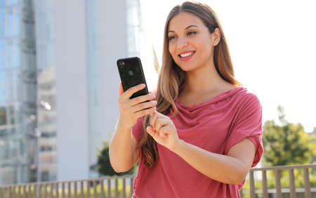 Portrait of happy friendly young woman using her mobile phone outdoors in a modern urban street