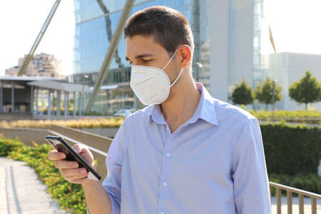 Business man with protective mask calling with smartphone in modern city Standard-Bild