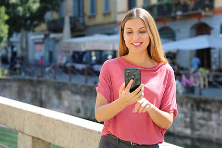 Smiling young woman chatting with mobile phone on Navigli canals in Milan, Italy