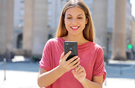 Gorgeous beautiful young woman with long hair chatting on smartphone in city street.