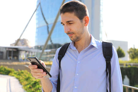 Young business man checking his mobile phone in modern city Standard-Bild