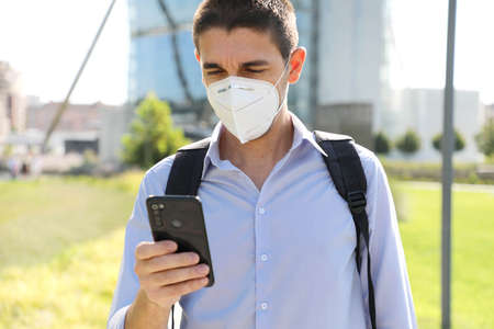 COVID-19 Young business man wearing protective mask using smartphone app in modern city street