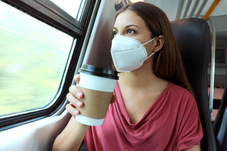 Young woman wearing protective face mask holding coffee cup on public transport. Business woman holding cup of coffee on train during pandemic. Standard-Bild