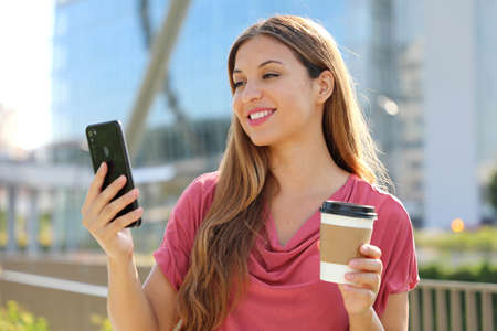 Smiling young brazilian woman wearing pink blouse video calling with smartphone outdoors, holding takeaway coffee cup