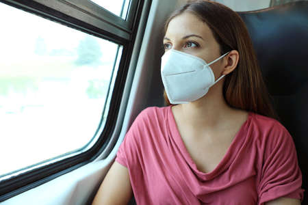Travel safely on public transport. Young woman with KN95 FFP2 face mask looking through train window. Train passenger with protective mask. Standard-Bild