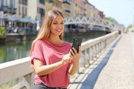 Smiling young woman scrolling messages on smartphone app to chat in Milan, Italy