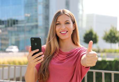 Happy beautiful woman thumbs up with smartphone in her hand and modern city on background. Positive businesswoman smiles at camera. Standard-Bild