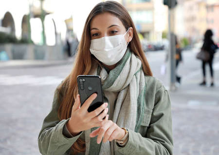 Young beautiful fashion woman wearing face mask in city street looks and typing on smartphone screen Standard-Bild