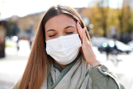COVID-19 Close up of young woman in city street wearing white surgical mask suffers from headache