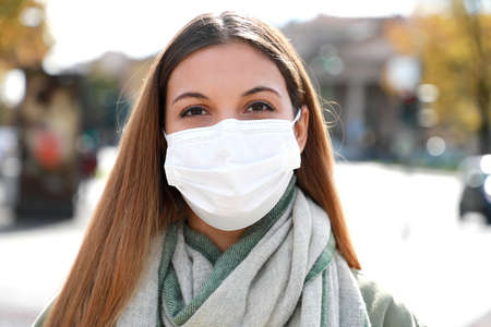 COVID-19 Close up of young woman in city street wearing white surgical mask looking at camera. Girl with protective mask on face against Coronavirus Disease 2019.