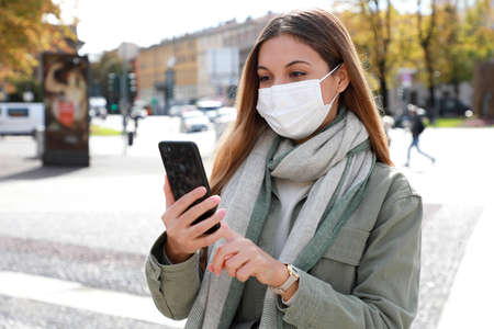 Portrait of young woman using smart phone in the city wearing face mask