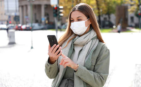 COVID-19 Mobile Application Young Woman Wearing Surgical Mask Using Smart Phone App in City Street